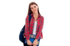 Portrait de jeune fille gaie d'étudiant avec le sac à dos et de dossiers pour des carnets d'isolement sur le fond blanc Images stock