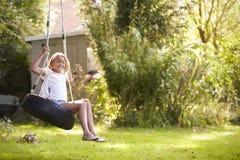 Portrait de jeune fille jouant sur l'oscillation de pneu dans le jardin Images stock