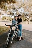 Portrait de jeune Guy Girl Couple Riding à la mode à la mode moderne beau attirant sur la vieille école de croiseur vert de moto images libres de droits