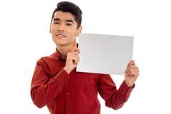 Portrait de jeune homme élégant dans le T-shirt rouge avec la plaquette vide dans des ses mains d'isolement sur le fond blanc Images stock