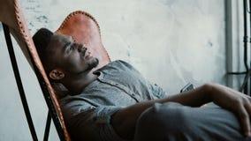 Portrait de jeune homme africain dans la chaise Le mâle est sérieusement pensée, tenant Smartphone Message de dactylographie de t photographie stock libre de droits