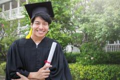 Portrait de jeune homme asiatique dehors son jour gradué Photo libre de droits