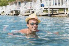Portrait de jeune homme avec la natation de chapeau de paille en mer photo stock