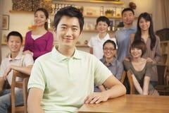 Portrait de jeune homme avec le groupe d'amis à un café Images stock