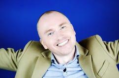 Portrait de jeune homme avec le sourire blanc comme neige Cheveux courts, manteau cr?me et un fond bleu ?motions et sourire image stock