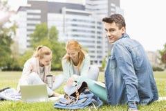 Portrait de jeune homme avec les amis féminins étudiant sur le campus universitaire Images libres de droits