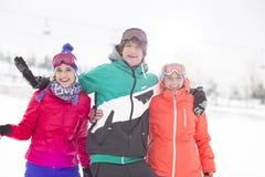 Portrait de jeune homme avec les amis féminins appréciant dans la neige Images libres de droits