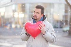 Portrait de jeune homme barbu avec une position en forme de coeur rouge de ballon sous la neige légère dans une rue de ville Hive photos stock