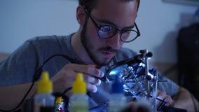 Portrait de jeune homme barbu réussi dans le fonctionnement en verre avec un fer à souder à son lieu de travail Concept de clips vidéos