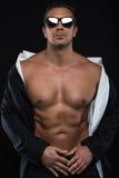 Portrait de jeune homme beau dans la position occasionnelle au-dessus du fond noir Images stock