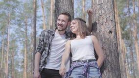 Portrait de jeune homme beau et jolie de femme regardant loin se tenants dans le concept de forêt de pin du camping loisirs banque de vidéos