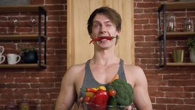 Portrait de jeune homme beau de sourire avec le poivre de piment dans sa bouche, se tenant derrière la table et les exploitations banque de vidéos