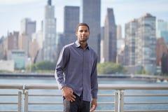Portrait de jeune homme bel d'Afro-américain avec l'horizon de NYC Photo stock