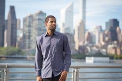 Portrait de jeune homme bel d'Afro-américain avec l'horizon de NYC Photos stock