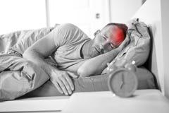 Portrait de jeune homme caucasien dans le lit avec le mal de tête photo stock