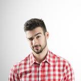 Portrait de jeune homme clignant de l'oeil avec son oeil droit Photographie stock libre de droits