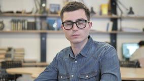 Portrait de jeune homme cr?atif en verres regardant l'appareil-photo banque de vidéos