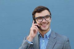 Portrait de jeune homme d'affaires bel heureux dans l'équipement formel parlant du téléphone portable, sur le fond bleu Bonnes no Images stock