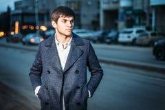 Portrait de jeune homme dans le manteau et la chemise blanche sur la rue dans la ville soirée photo libre de droits