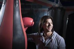 Portrait de jeune homme de sourire au gymnase de boxe se penchant sur le sac de sable photographie stock