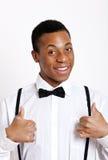 Portrait de jeune homme faisant des gestes des pouces au-dessus du fond blanc Images stock