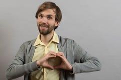 Portrait de jeune homme faisant le geste de coeur Images stock
