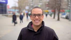 Portrait de jeune homme heureux avec des verres regardant à l'appareil-photo et souriant sur le fond de ville Fermez-vous vers le clips vidéos