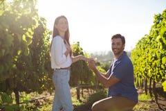 Portrait de jeune homme proposant l'amie au vignoble Image libre de droits