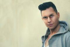 Portrait de jeune homme sérieux se penchant contre le mur Coiffure de mode photographie stock libre de droits