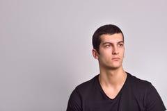 Portrait de jeune homme sérieux se tenant sur le fond gris Image libre de droits
