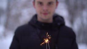 Portrait de jeune homme de sourire dans la veste chaude avec le cierge magique brûlant en parc d'hiver Foyer changeant du visage  clips vidéos