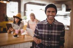 Portrait de jeune homme de sourire tenant des lunettes se tenant contre les amis féminins au café Photographie stock