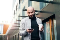 Portrait de jeune homme de sourire utilisant le smartphone sur la rue de ville L'homme envoie le message textuel lifestyle R?seau photos stock