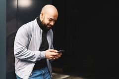 Portrait de jeune homme de sourire utilisant le smartphone sur la rue de ville L'homme envoie le message textuel lifestyle R?seau photographie stock libre de droits