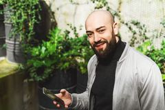 Portrait de jeune homme de sourire utilisant le smartphone sur la rue de ville L'homme envoie le message textuel lifestyle R?seau images libres de droits