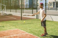 Portrait de jeune homme sur le court de tennis d'école de campus d'été photo stock