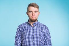 Portrait de jeune homme triste sur le fond bleu Photo stock