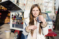 Portrait de jeune jolie femme avec une tasse de boisson chaude sur le fond ensoleillé d'extérieur image libre de droits