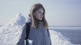 Portrait de jeune jolie femme blonde dans la position chaude de veste sur le glacier avec la carte dans des mains, regardant auto banque de vidéos