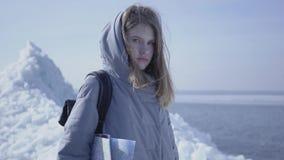 Portrait de jeune jolie femme blonde dans la position chaude de veste sur le glacier avec la carte dans des mains, regardant in c clips vidéos