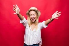 Portrait de jeune jolie femme dans le chapeau de paille avec les paumes ouvertes, d'isolement sur le fond rouge photos libres de droits