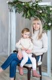 Portrait de jeune mère ainsi qu'un petit enfant dans un intérieur de chambre Image stock