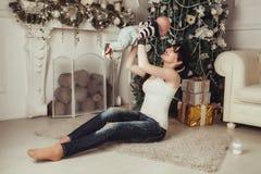 Portrait de jeune mère heureuse avec l'enfant dupant autour près de l'arbre et de la cheminée de Noël La femme tient le bébé au-d Photos stock
