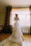 Portrait de jeune mariée élégante heureuse de brlonde dans le voile et la longue robe blanche de luxe se tenant près de la fenêtr Photographie stock