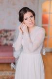 Portrait de jeune mariée avec du charme dans la robe de mariage Belles jeunes femmes habillant ses boucles d'oreille se préparant Image stock