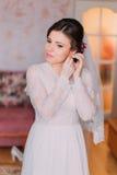 Portrait de jeune mariée avec du charme dans la robe de mariage Belles jeunes femmes habillant ses boucles d'oreille se préparant Photo libre de droits