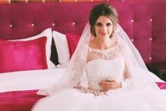 Portrait de jeune mariée sur le lit cramoisi Images stock