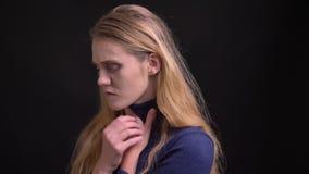 Portrait de jeune modèle blond triste avec des cheveux de duvet souffrant de la grippe et toussant sur le fond noir banque de vidéos