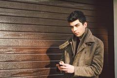 Portrait de jeune modèle masculin turc beau de brun méditerranéen de course dans le manteau en cuir utilisant le téléphone d image stock