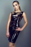 Portrait de jeune modèle mince magnifique avec la queue de cheval et le maquillage artistique portant la robe d'or de paillette b images libres de droits